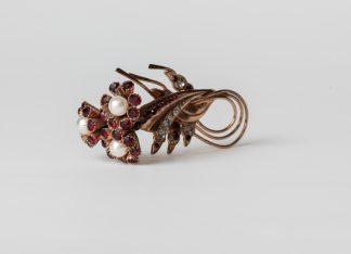 Broche de metal con piedras de granate y perlas.