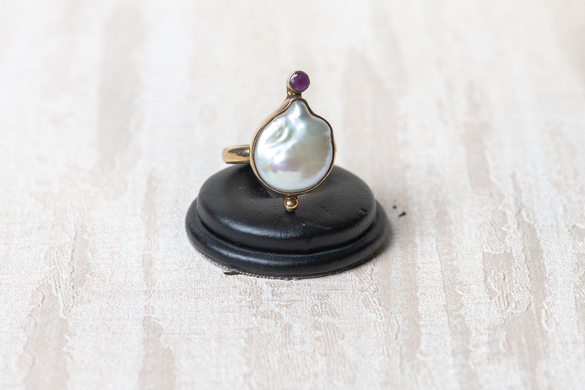 Anillo de plata dorada con una perla de agua dulce y un rubí